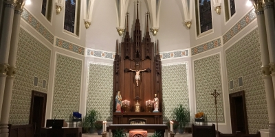sanctuary and altar with tabernacle and candles in front of crucifix